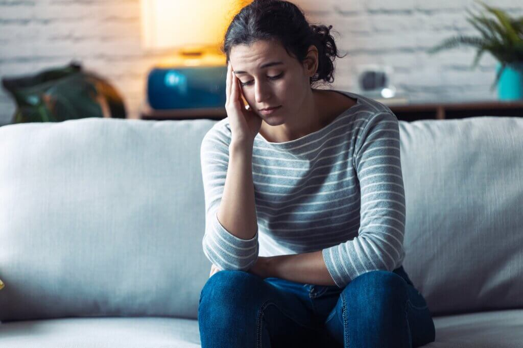 Worried young woman thinking while sitting on sofa in the living room at home.