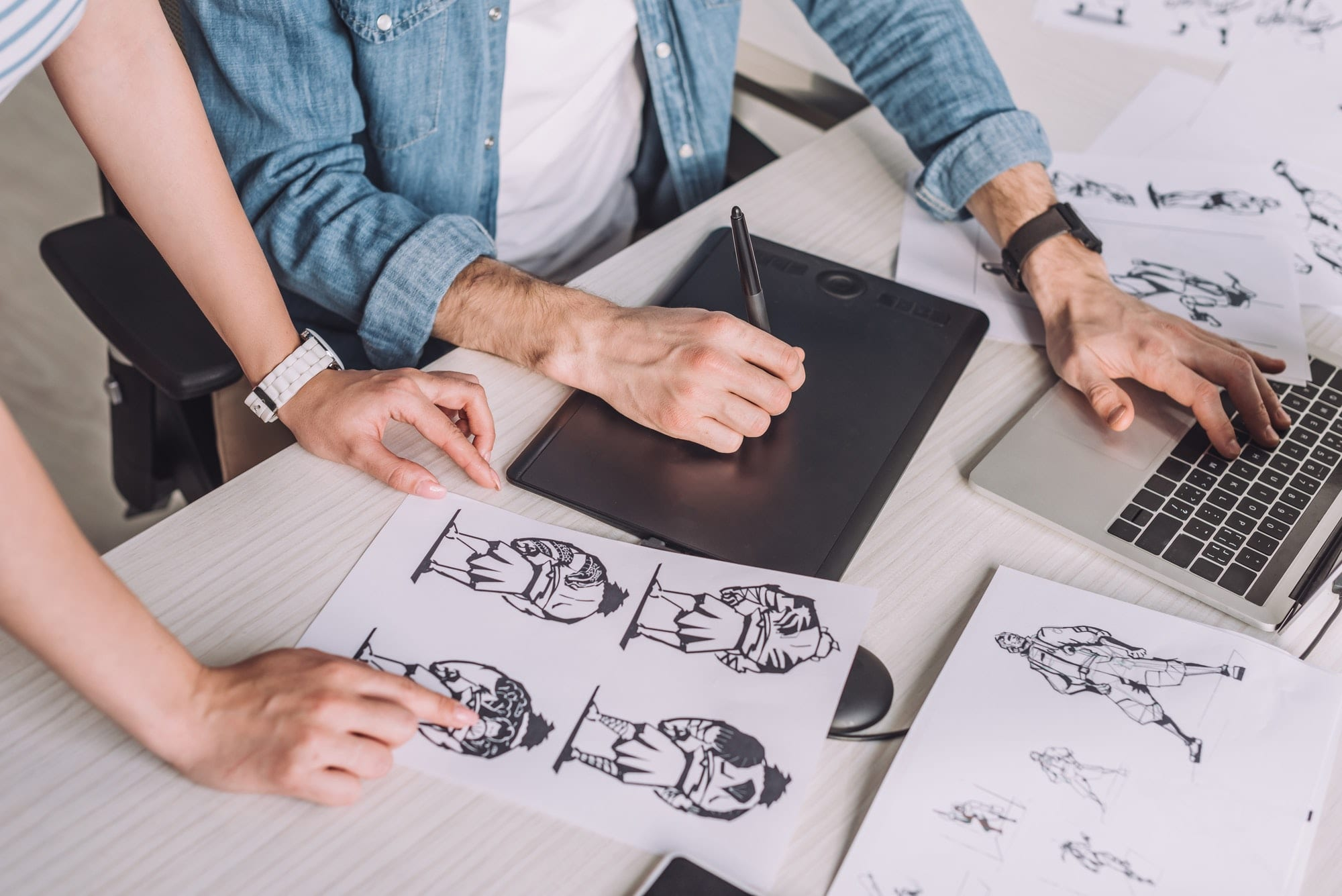 cropped view of illustrator pointing with finger at cartoon sketch near coworker