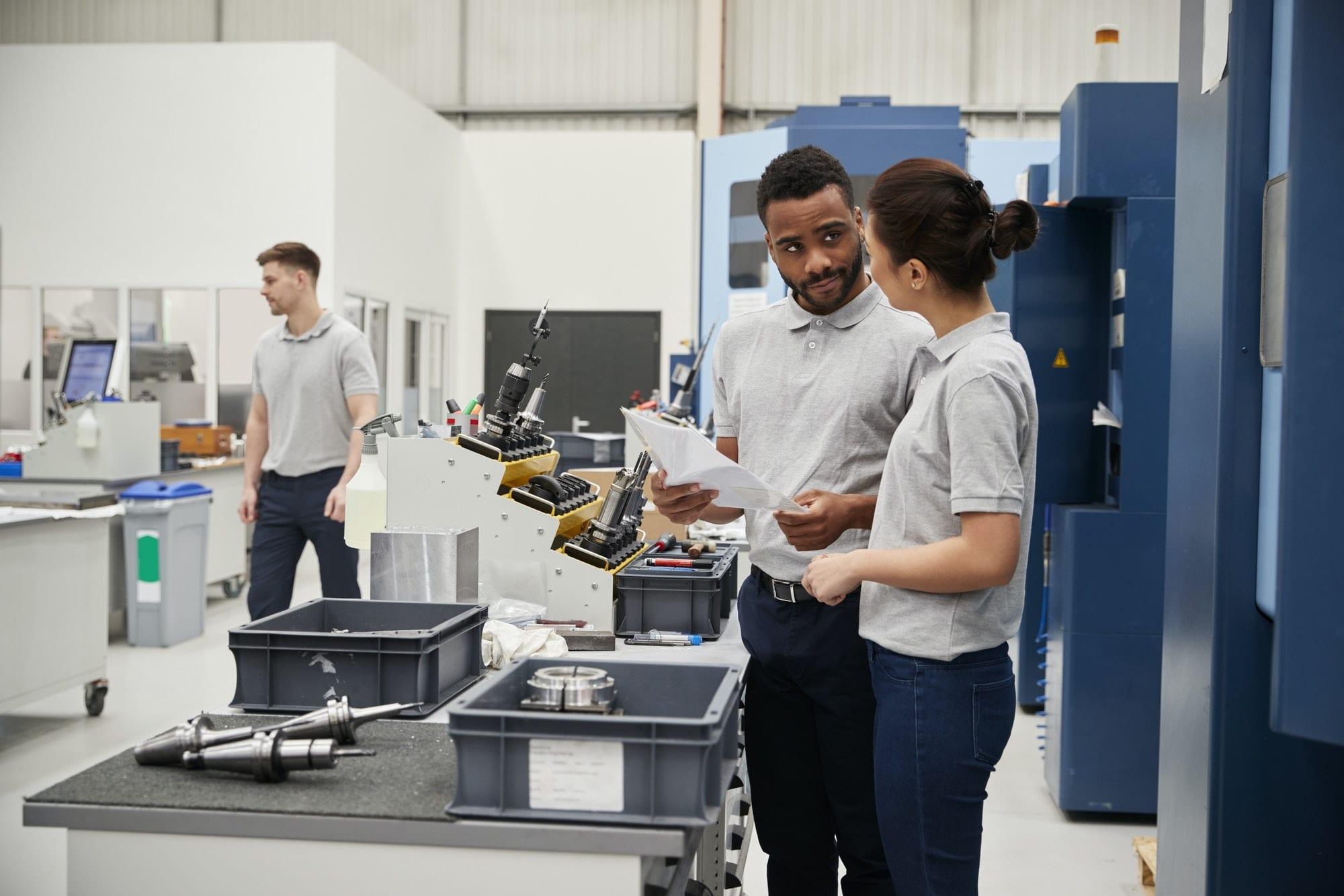 Engineer And Apprentice Meet On Floor Of Engineering Workshop