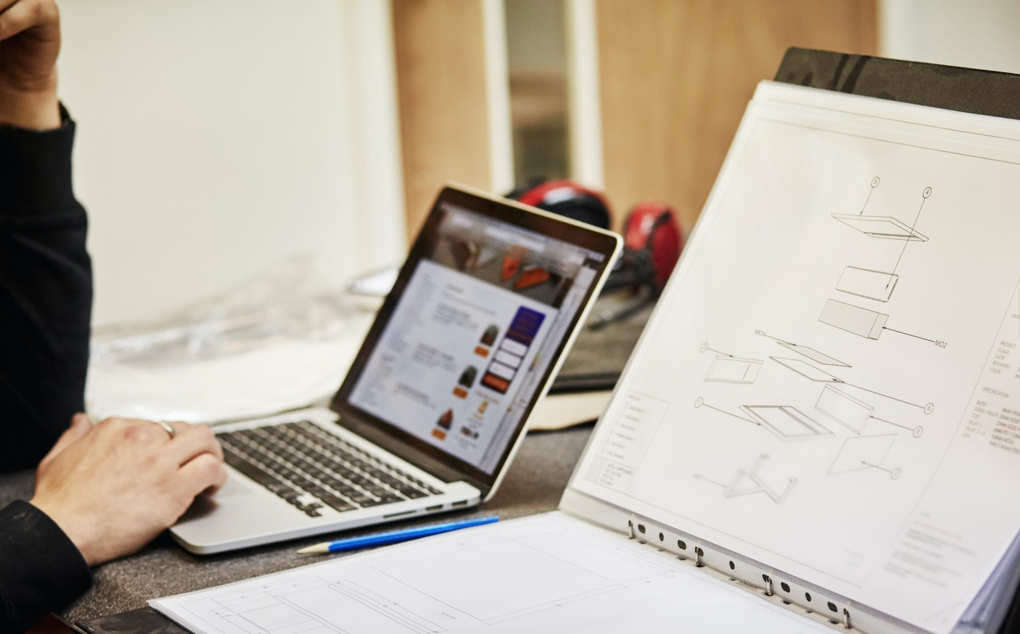Furniture designer with sketches and laptop