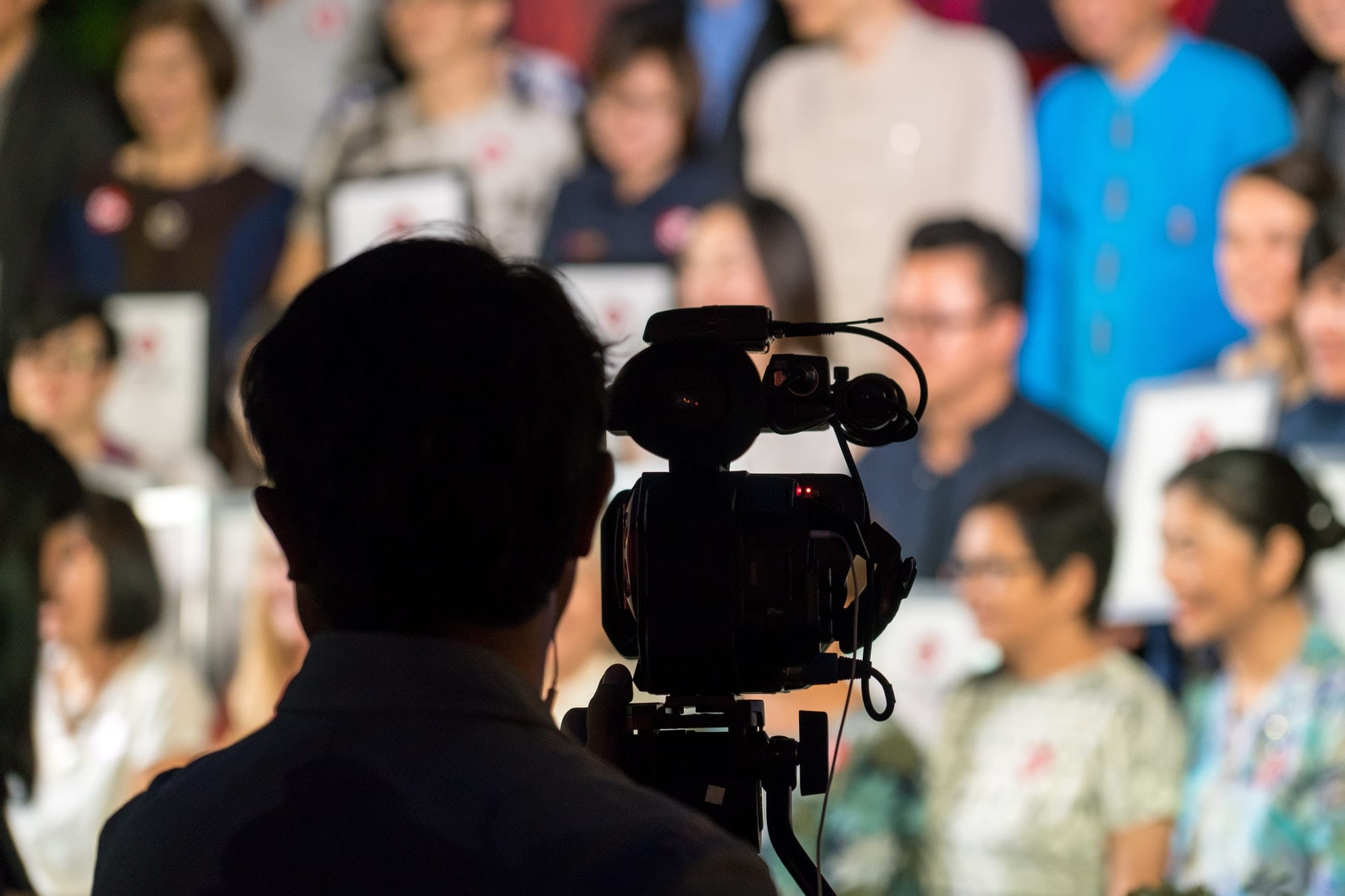 Silhouette of professional camera man from behind with audience of men and women sitting background.