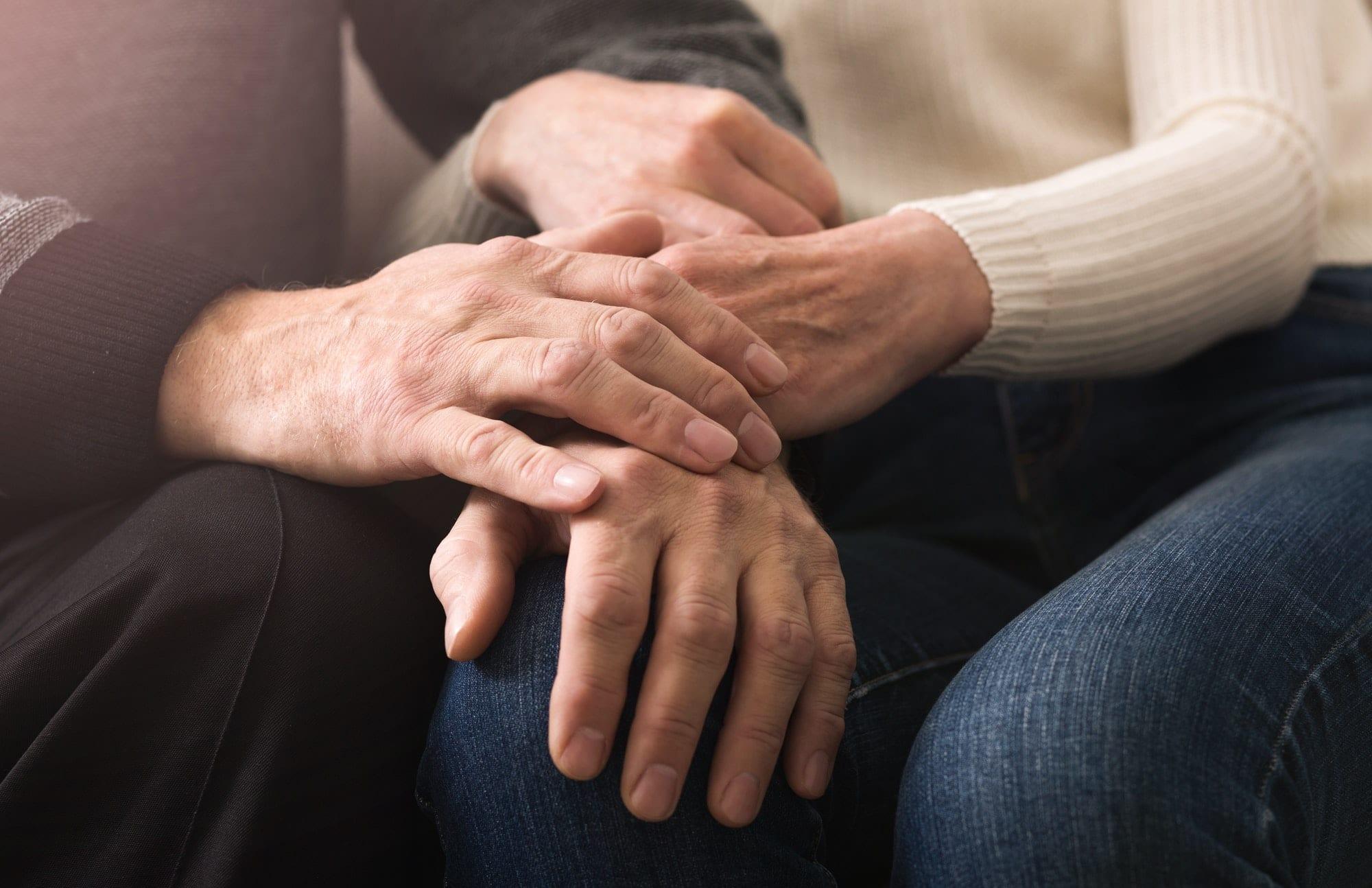 Together till end. Elderly couple holding hands