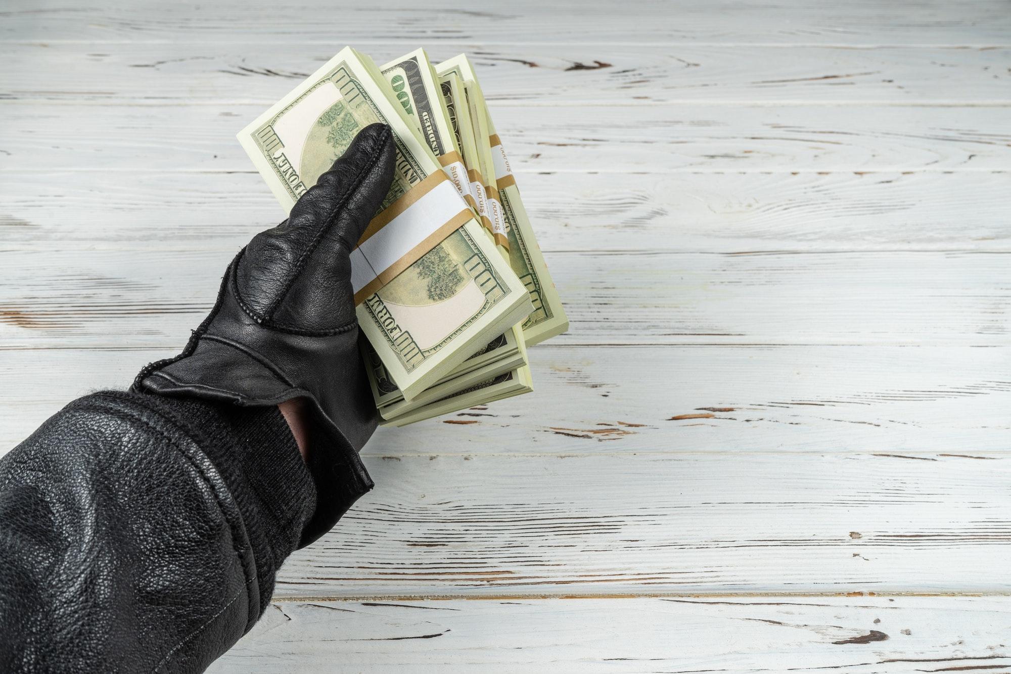 Man In Black Leather Gloves Holding Bricks Of Money